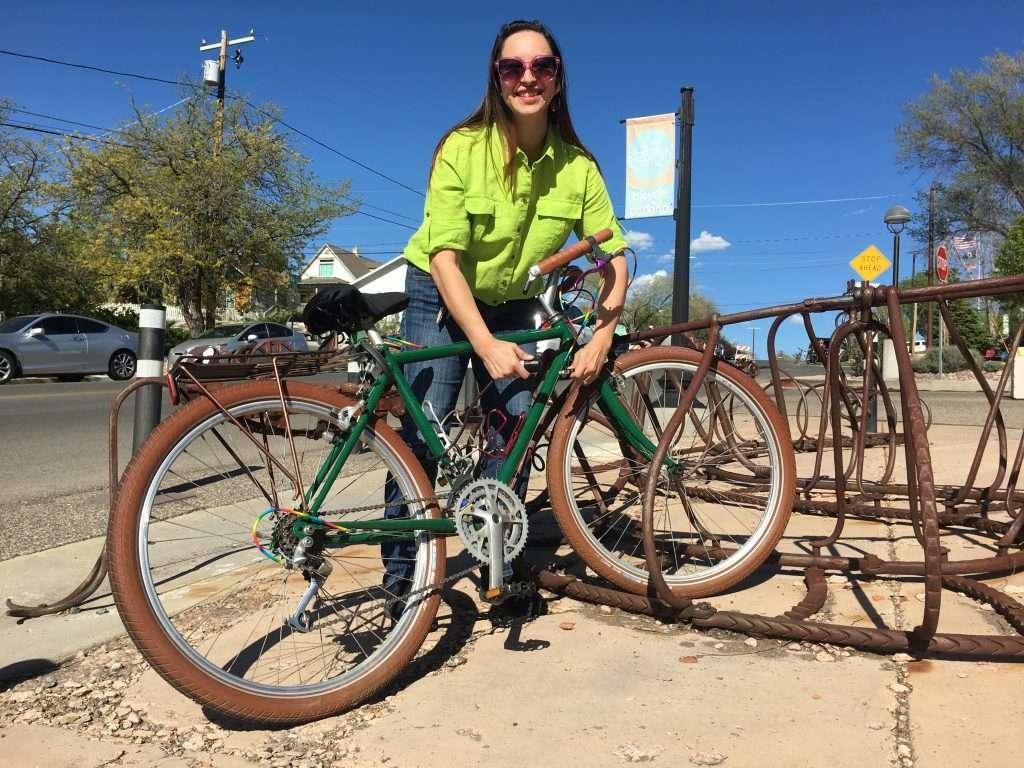 patron parking bike along Goodwin Street at the large rattlesnake bike rack sculpture