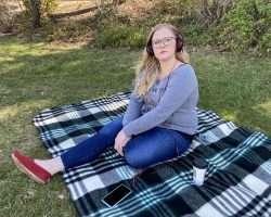 Woman seated on blanket outdoors, wearing headphones