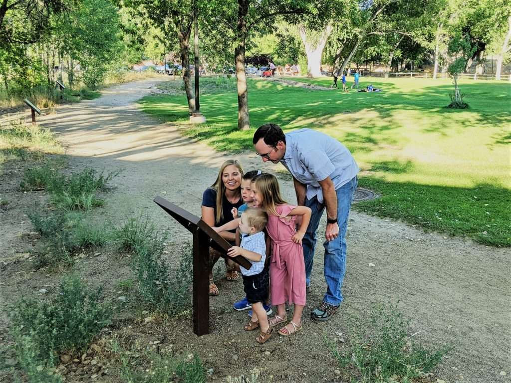 A young family gathers around a storybook panel at Granite Creek Park.